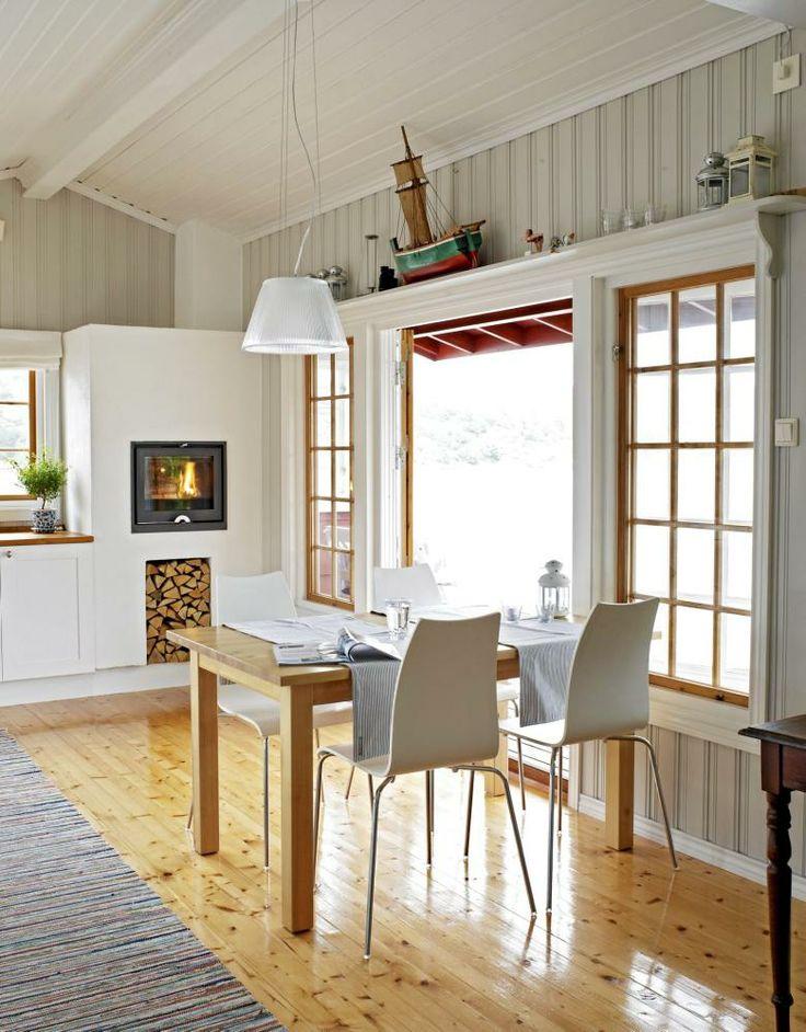 Fra kjøkkenet åpner de doble glassdørene seg mot en stor terrasse og det gråblå havet. Innebygd peisovn til kjøkkenet er fra Jøtul, mens taklampen Romeo Moon er fra Flos.