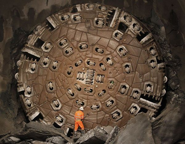 A miner climbs on excavated rocks after a giant Sissi drill machine broke through the last section of rock at the construction site of the NEAT Gotthard Base Tunnel in Switzerland on March 23, 2011. Crossing the Alps, the world's longest train tunnel consists of two, parallel, single-track tunnels, each a length of 35 miles. The project should become operational at the end of 2016.