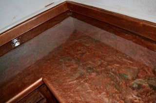 Resurfaced old laminate countertops with Epoxy and metallic paint from www.countertopepoxy.com.  $300 for my whole kitchen.  They look amazing!  Copper with patina accents.  DIY!!  If I can do it, anyone can.