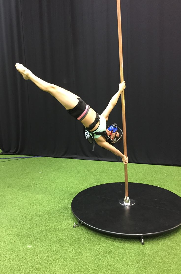 Pole dancer in Iron X position, fitted with K5 wearable metabolic equipment for the measurement of oxygen consumption and other parameters.