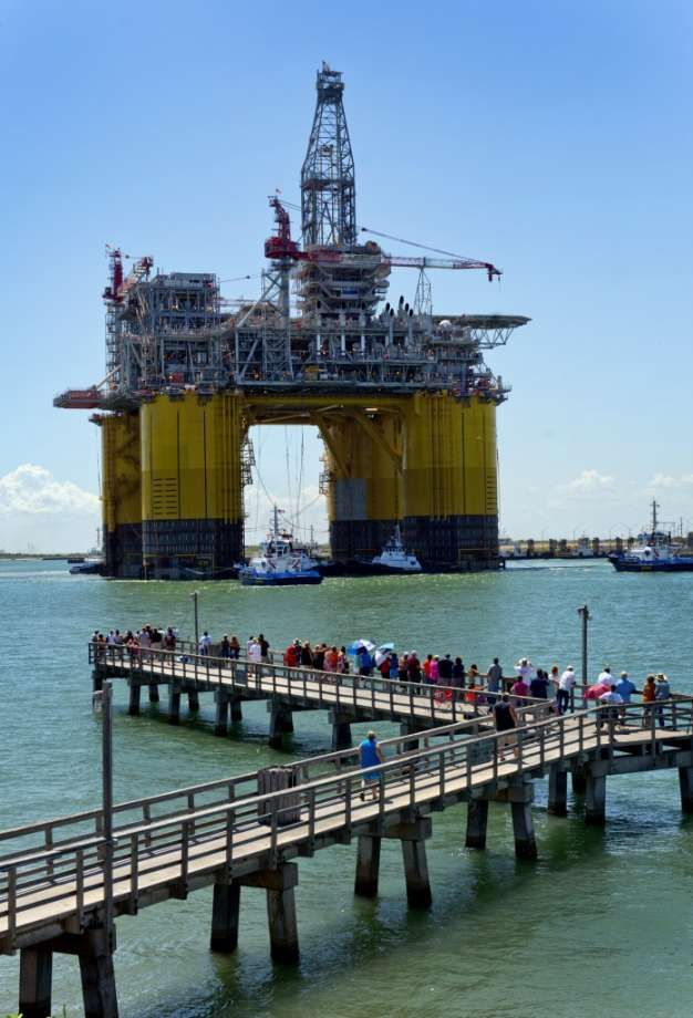 People gather on a dock to watch the Royal Dutch Shell Plc Olympus tension leg platform (TLP) set sail from Kiewit Offshore Services in Port Aransas, Texas, U.S., on Saturday, July 13, 2013. Olympus, Shell's biggest constructed tension leg platform, started the ten day, 425-mile voyage to Mars B Field in the Gulf of Mexico on July 13. Photographer: Eddie Seal/Bloomberg Photo: Eddie Seal, Bloomberg