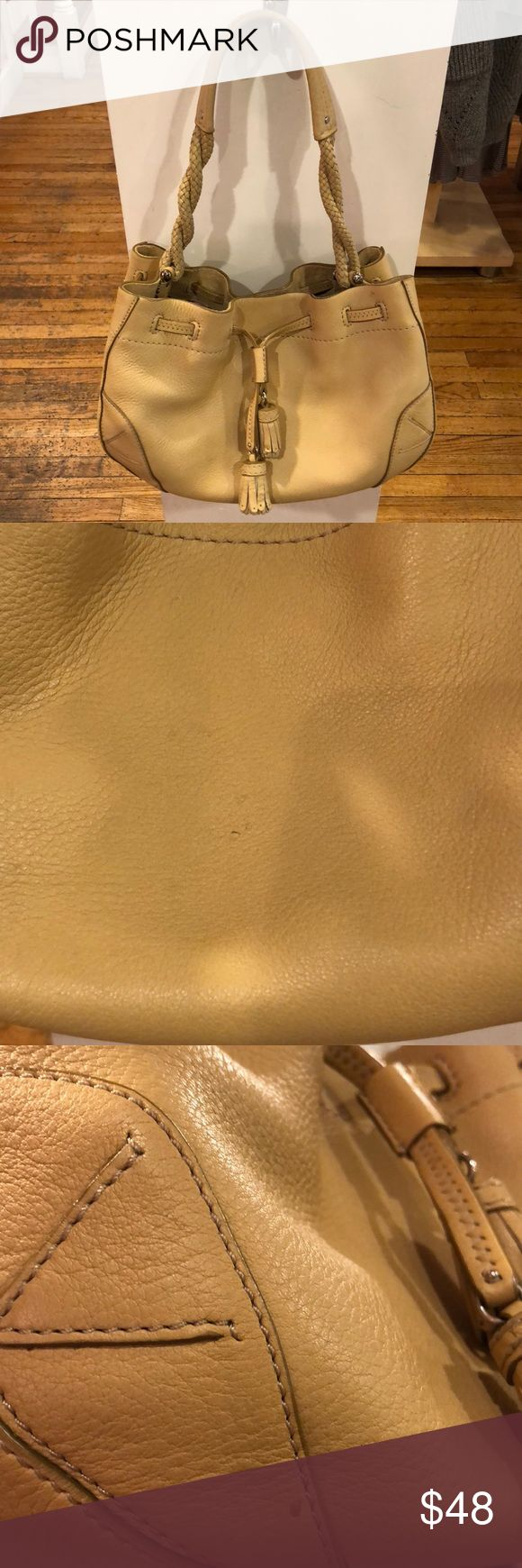 """Cole Haan Tan Leather Bag This call on tan leather drawstring bag has tassel details and braided twisted handles. Used condition but lots of life left! A great medium sized bag. Visible wear is pictured.  Measures approximately 13"""" L x 7.5"""" H x 7"""" W  Feel free to ask any questions! I accept reasonable offers. Cole Haan Bags"""