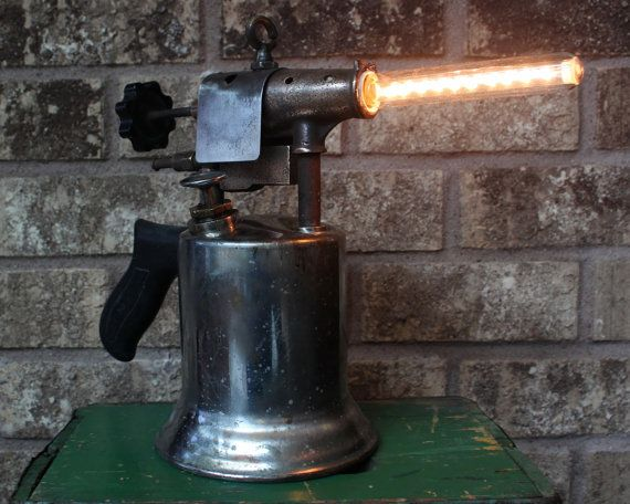 This beautiful one of a kind custom table lamp will spruce up your man cave décor with an industrial chic backdrop. It is based on a vintage chrome / brass blow torch with a bulb in the center to simulate the flame.