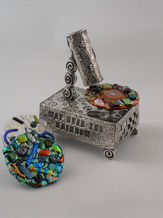"Alice Alper-Rein. Way Over the Rainbow - A Musical Kaleidoscope    4"" tall x 2"" wide.  Fine silver metal clay, brass, sterling silver, dichroic glass.  The music box mechanism spins the interchangeable wheels which are viewed through the kaleidoscope mechanism."