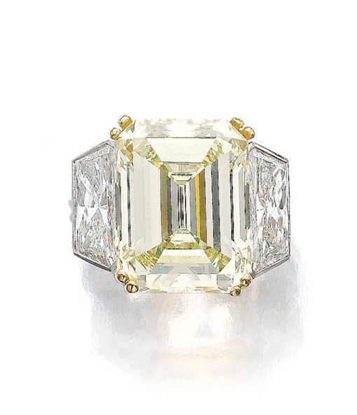 FINE FANCY LIGHT YELLOW DIAMOND AND DIAMOND RING. The step-cut fancy light yellow diamond weighing 14.48 carats, double claw-set between trapeze-shaped diamond shoulders, size 48.