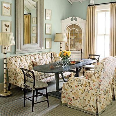 Enveloped in Comfort | The worn black finish on the distressed wood dining table contrasts with the elegant floral fabric covering the sofa and club chairs, adding depth to the room. | SouthernLiving.com