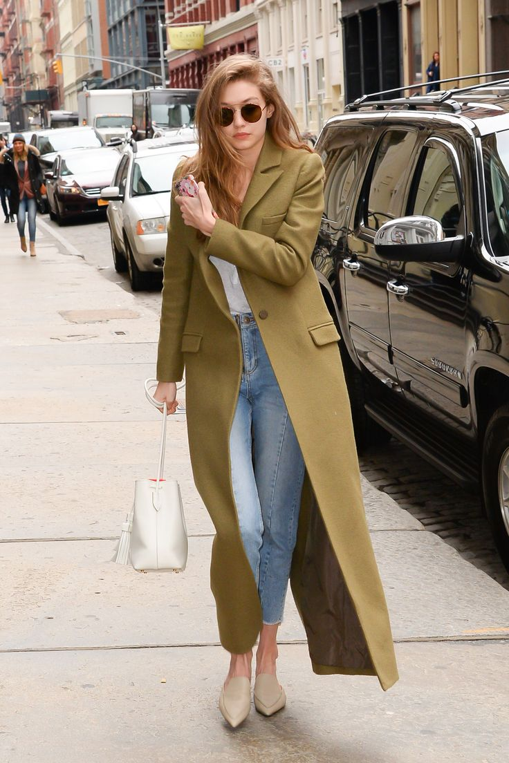 January 27, 2017  In a floor-length olive green coat, white tee, high-waisted jeans, pointed-toe flats, white Mansur Gavriel bucket bag and round sunglasses while out in New York.