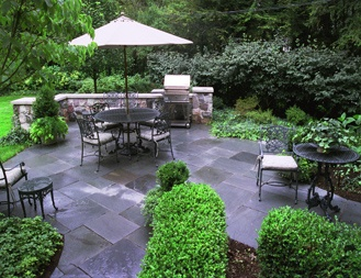 A built-in grill, hedges and greenery split up this large patio - www.fourseasonsgardencenter.com - Michigan