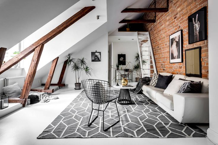 Monochrome living room in Scandinavian penthouse with exposed brick wall