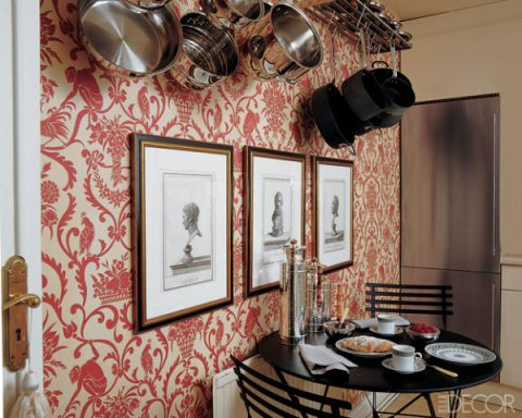 In the kitchen of this London flat designed by Alex Papachristidis, 19th-century neoclassical prints from John Rosselli International are displayed against Nina Campbell's Tamarin wallpaper from Osborne & Little.