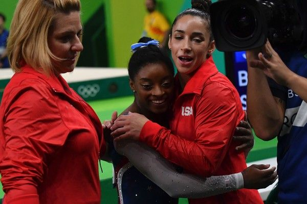 US gymnast Simone Biles (C) embraces US gymnast Alexandra Raisman (R) after seeing her score in the uneven bars event of the women's individual all-around final of the Artistic Gymnastics at the Olympic Arena during the Rio 2016 Olympic Games in Rio de Janeiro on August 11, 2016. / AFP / Ben STANSALL