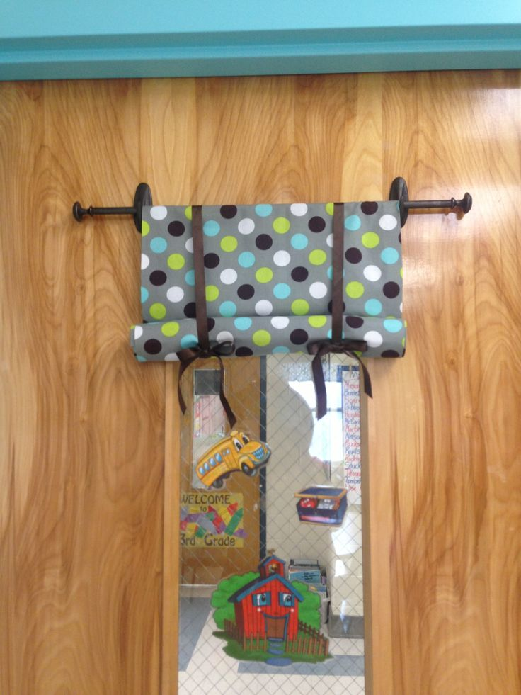 """My no-sew easy to move """"safety-curtain"""" for my classroom door. It is a dowel rod and command hooks spray painted with oil rubbed bronze and drawer pulls hot glued to the ends. A no-sew curtain long enough to cover the door and then some is draped over the rod so the pattern shows from the outside too. Then I rolled up the material and then used Velcro to attach the ribbons. Now I can quickly cover my classroom door window if needed."""