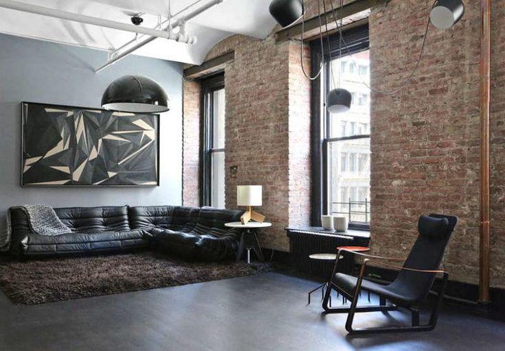 Das Wohnzimmer hat eine schwarze Ecksofa, eine große Aussage Kunstwerk und ein flauschiger Teppich