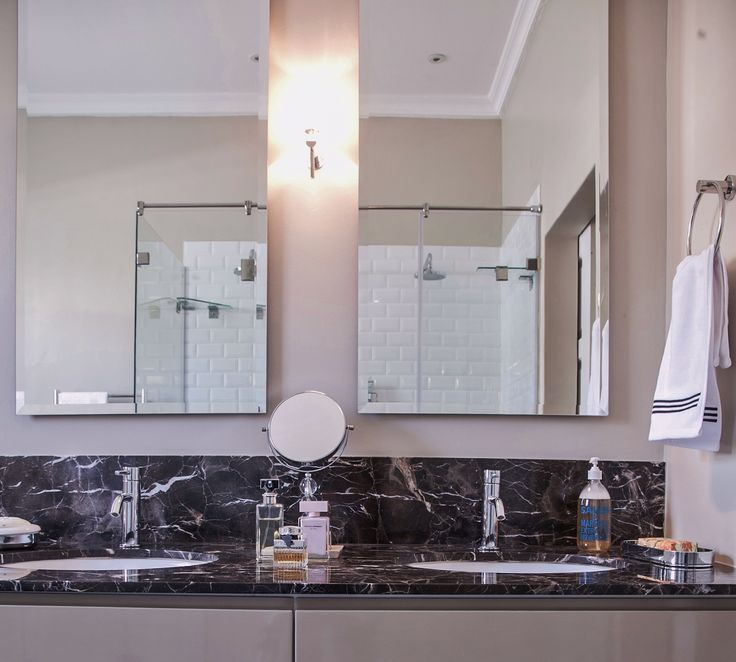 The Marron Emperador marble top with underslung basins works well with the beveled mirrors with de misting pads and Astro wall lights.