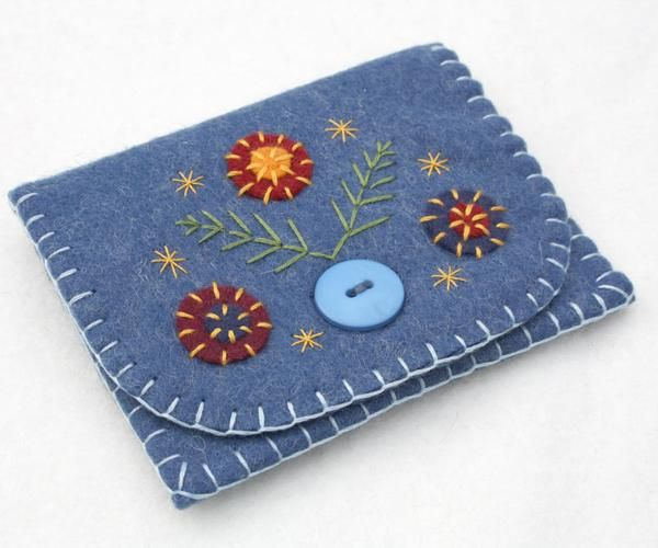 Handmade felt coin purse with embroidered and appliqued flowers and leaves. Made in blue felt with light blue lining, blanket stitched edges and button fastening. For coins, cards, jewellery or other