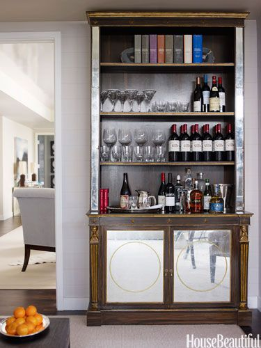 Antique bookcase doubles as a bar. Design: Phoebe and Jim Howard. housebeautiful.com. #bookcase #home_bar #antique