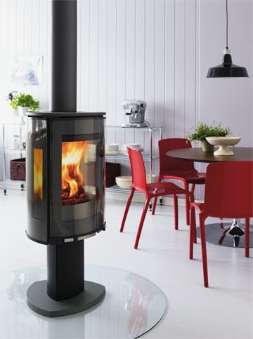 Modern woodstove - maybe we could fit this in the corner by the window. I love that it is up higher on a pedestal. Mmmm, toasty!