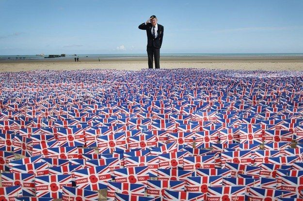 WWII veteran Fred Holborn salutes as he looks at British Legion Union flags carrying thank you messages planted in the sand on Gold Beach near Asnelles, France.