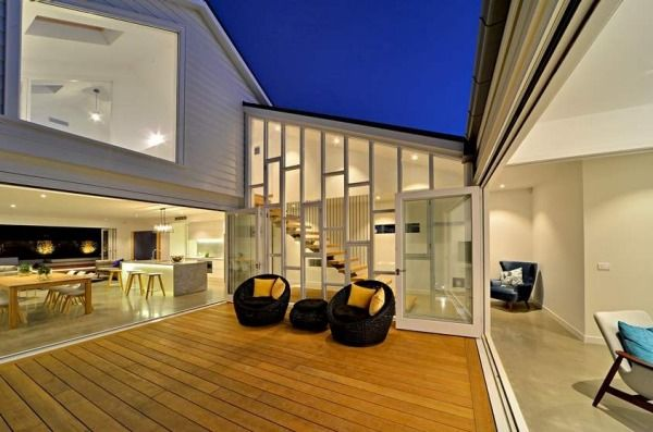 A double-height atrium with a fully glazed wall and wide openings to the living areas on either side of the courtyard ...
