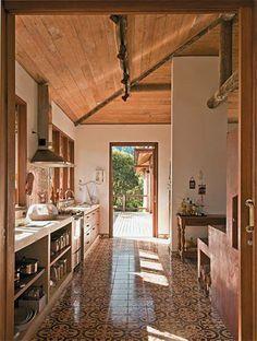 A tradição caipira do forno a lenha e dos ladrilhos hidráulicos (Dalle Piagge) marca a cozinha. Em contraponto, a bancada é de concreto – executado na obra. O forro de peroba (marceneiro Emerson Pascoaleto) acompanha a inclinação do telhado.