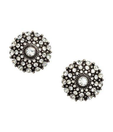Mörkgrå. Ett par runda örhängen i metall med strasslipade stenar. Diameter 3 cm.