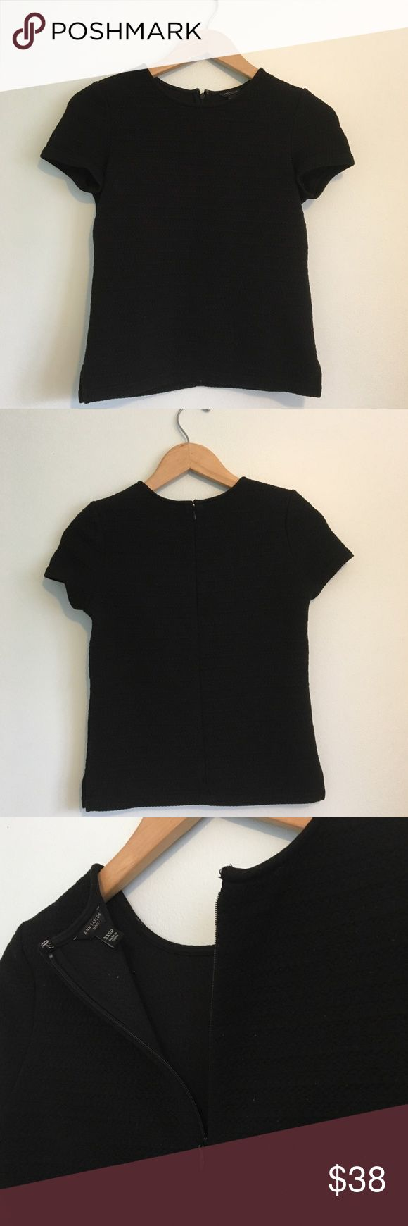 Ann Taylor Petite Black Textured Short Sleeve Top This stylish top is from Ann Taylor's petite line of women's clothing. The fabric is thick and has a unique knit texture (see pictures for details). Zipper on the back, with a hook and eye closure. Small slit on the sides.   Perfect top for work, school, or every day wear. Would look excellent with a structured blazer or a full skirt.  XXS Petite  Used, in excellent condition! Ann Taylor Tops