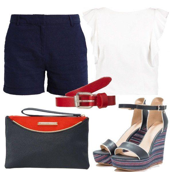 Outfit composto da shorts navy, blusa bianca con volant e zeppe con cinturino alla caviglia. Completano il look la cintura rossa in pelle e la borsa a mano bicolor.