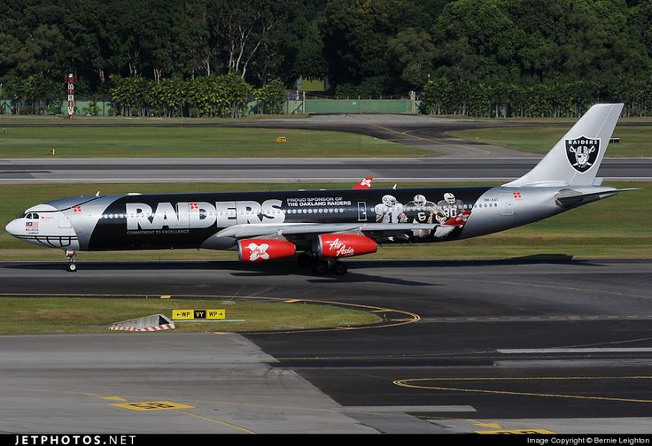 AirAsia X (MY) Historic fleet, Airbus A340-313 9M-XAC aircraft, painted in ''Oakland Raiders'' special colours Jun. 2009 - Jun. 2012, the stickers ''Commitement to Excellence-Proud Sponsor Of The Oakland Raiders'' & the sticker photo of players on the airframe, skating at Singapore Changi International Airport. 03/02/2010. (Oakland Raiders=a professional American football franchise).