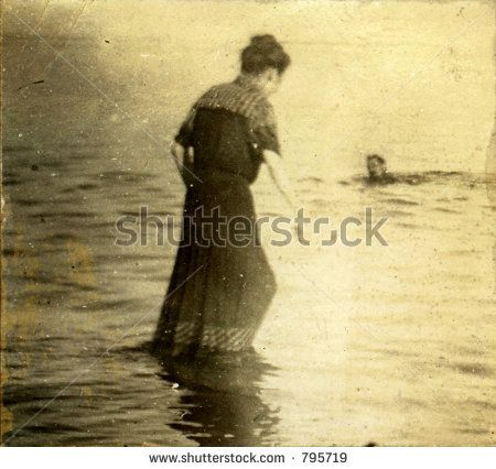 Vintage woman wading in towards submerged swimming man. Circa 1910. Photo very old with many scratches, fading, and solarizing qualities. by Elena Ray, via ShutterStock