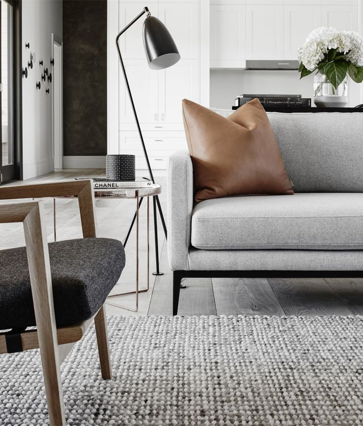 Pale light grey sofa with black metal frame legs, tan leather scatter cushion, grey timber floorboards, grey rug, black floor lamp, walnut armchair with dark charcoal grey cushion, white shaker cabinets, white glass splashback