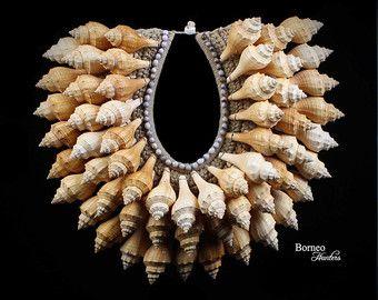 Papoea-Nieuw-Guinea crème touw ketting, samengesteld uit zes degressieve halve manen van witte koraal Shell drop hangers. De kraag is ingericht met vier rijen van Nassa Tompoucen en aan elke kant van de ketting zijn vijf gedessineerde lus strengen van bruin houten kralen, Jobs scheur zaden en Nassa schelpen. De zes degressieve koralen zijn tussen 2.9 en 3.5 duim in breedte. De binnendiameter van de band van de ketting is 4,5 inch x, en de buitendiameter is 8,5 inch. De ketting is 9.7 inch…