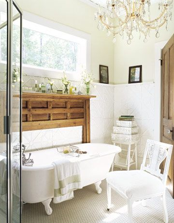 dream bathroom: chandelier + clawfoot tub + rustic wood mantle