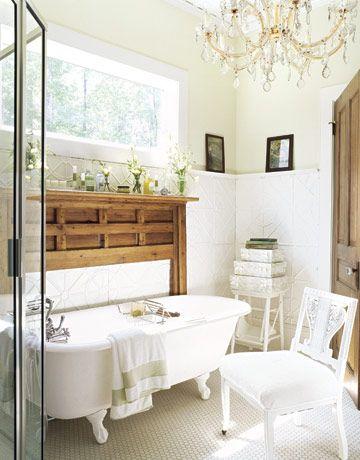 dream bathroom: chandelier + clawfoot tub + rustic wood mantle