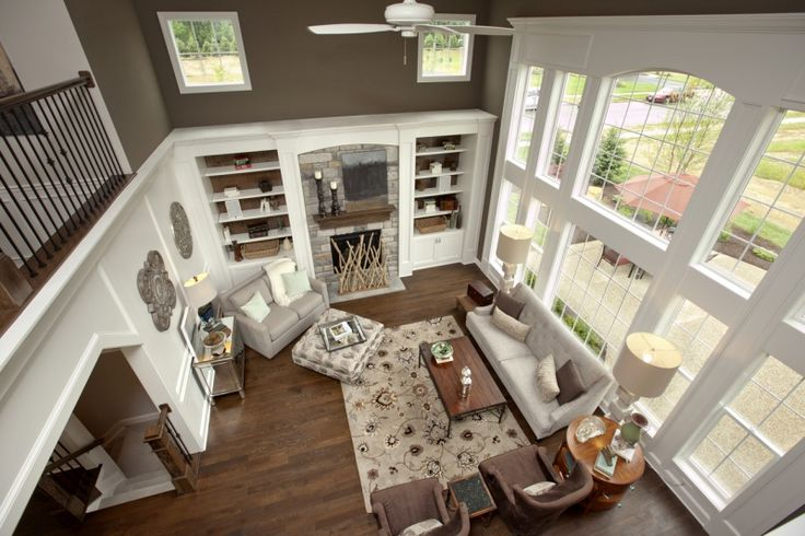 Grand Two Story Great Room by 3 Pillar Homes. These large windows allows you to maximize on the natural light coming in making the room light and bright. Our craftsmanship is shown here with crown molding, heavy trim around the windows, built-ins, and wainscoting.