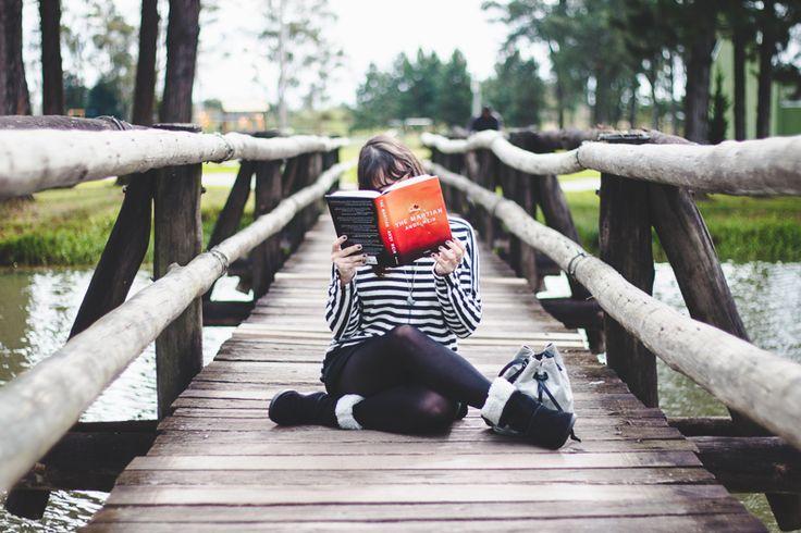 Resenha do livro Perdido em Marte (The Martian) de Andy Weir.  Garota sentada em uma ponte de madeira usando moletom listrado, saia preta, meia calça, bota e lendo um livro.