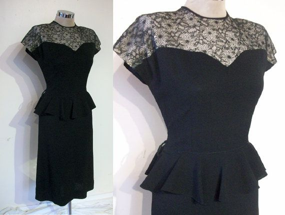 Ladies, this has to be the all time best flirty, fetching forties dress. Original 1940s, its in a charcoal black rayon crepe, with a silhouette and details designed to turn heads. The bodice is fitted with waist darts front and back and buttons down the back, and an adorable sweetheart outline is set into a fantastic nude-lined lace illusion yoke that stretches across the padded shoulders and into the sweet little cap sleeves; below, the a- line skirt is set with a fluttering peplum over the…