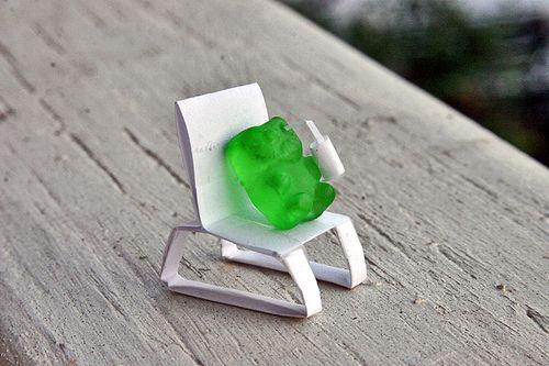 Gummy bear sitting on an origami chair drinking an origami daiquiri