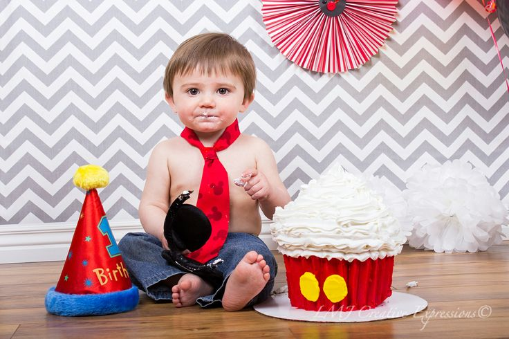 1-year old cake smash in Colorado Springs. Cute baby boy during his Mickey Mouse inspired Cake Smash. Baby Photography Colorado Springs, CO