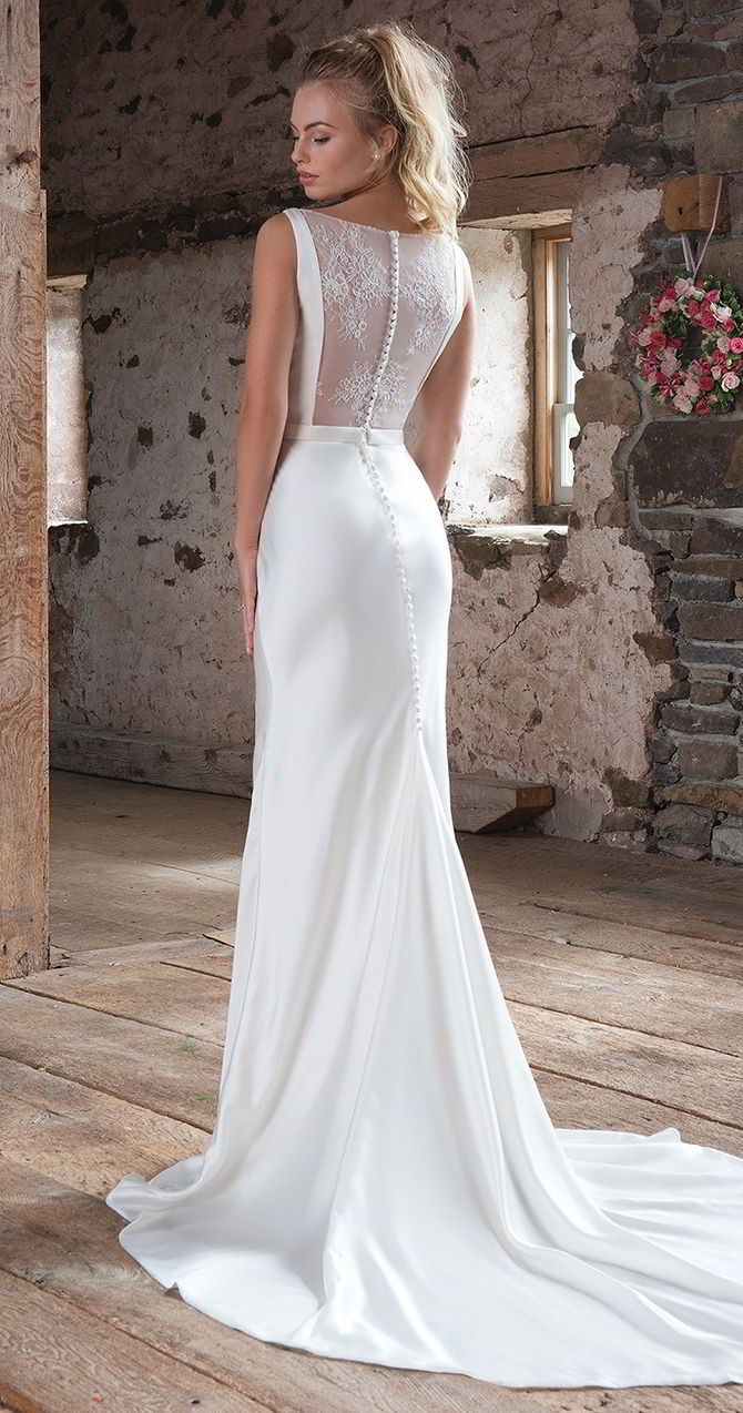 A sweet and simple gown with flirty back details. This high-neck style has a simple belted waist, a square-cut illusion lace back and feminine slim a-line gown.