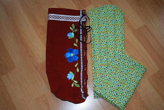 This is a beautiful traditional native american moss bag for wrapping up baby. Outer layer is made with a rusty brown colored corduroy and has gorgeous floral applique in royal blue. Lining and swaddle fabric are an adorable floral print on a light green background. Lacing is genuine