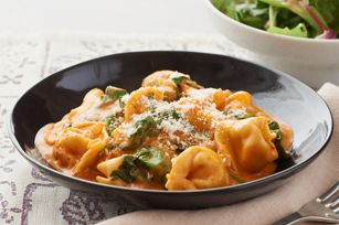 Tortellini in Creamy Rosé Sauce ■1Tbsp. olive oil  ■1onion, chopped  ■1clove garlic, minced  ■1-1/2cups fat-free reduced-sodium chicken broth  ■1cup spaghetti sauce  ■1pkg. (9 oz.) refrigerated cheese tortellini  ■1/2cup PHILADELPHIA Original Cooking Creme  ■4cups loosely packed baby spinach leaves  ■1/4cup KRAFT Grated Parmesan Cheese