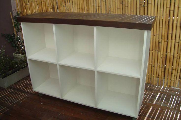 Mueble/mesada color blanco con ruedas, amplios estantes y tapa de madera
