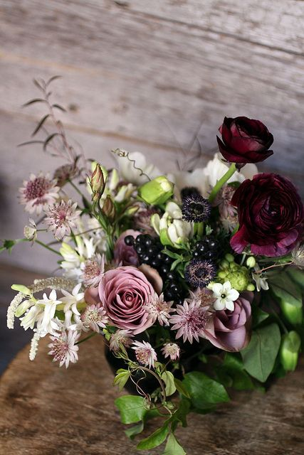 Dark glistening berries, green foliage and flowers going from dark red to deep pink to white.