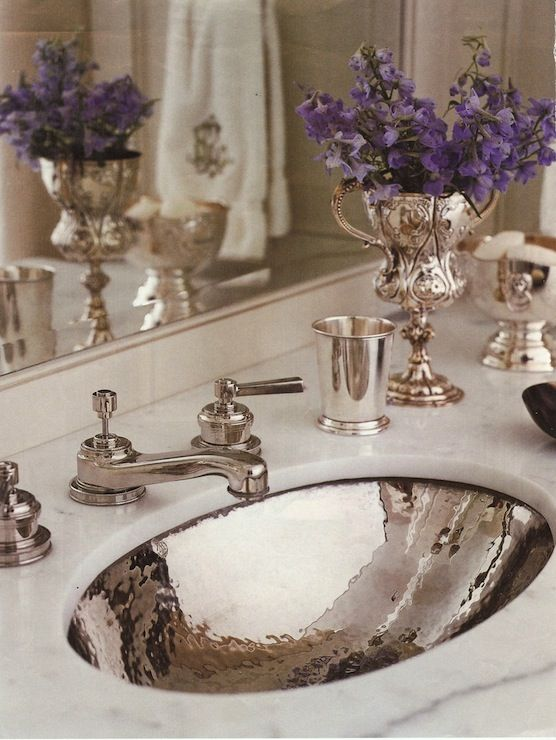Carrera marble vanity with a hammered silver sink, silver faucet and accessories, trophy with flowers - Circa Interiors  Antiques - Jane Schwab, Designer - Photo by Michael Parteno