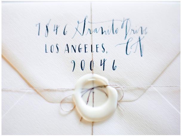 Puur witte uitnodigingen in handgeschept papieren enveloppen met een wit waxzegel erop!