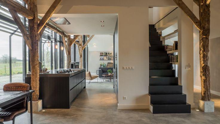 Het witte volume met kookeiland, kastenwand, trap en studie staat decentraal in de boerderij. Achter de kastenwand loop je via een stalen trap naar de studie erboven.