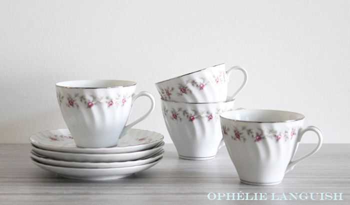 Charmingly shabby chic set of four white vintage tea cups and saucers. Swirl pattern featuring a pink rose garland motif with silver trim. A perfect set for a shower or tea party.