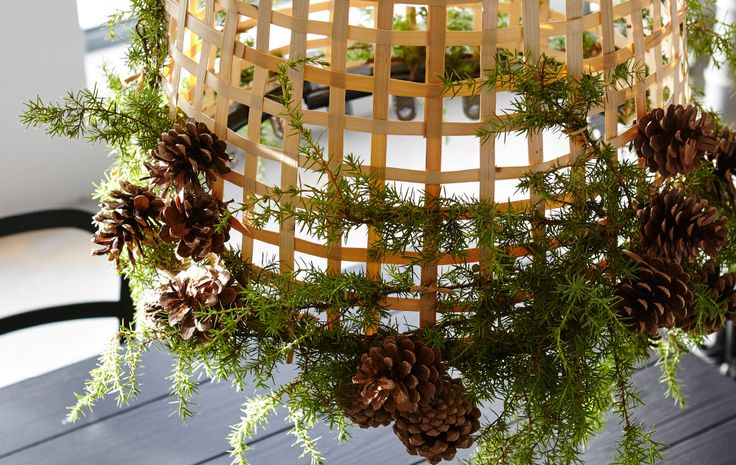 An IKEA GADDIS basket is decorated with greenery and pine cones and hung as a lamp.