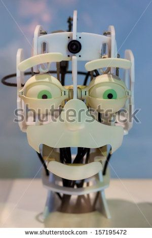 Head of a robot with funny green eyes and a funny expression. His mounth is open with a camera located on top of the cyborg head