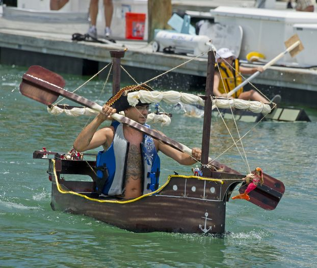 "In this photo provided by the Florida Keys News Bureau, a contestant in the Schooner Wharf Minimal Regatta paddles his pirate ship Sunday, May 25, 2014, in Key West, Fla. Nearly two dozen teams staged the wacky ""sink or swim"" regatta. Rules required entrants to build a boat out of a 4-by-8-foot sheet of plywood, two 8-foot-long two-by-fours, a roll of duct tape, a pound of fasteners and epoxy paint. (AP Photo/Florida Keys News Bureau, Rob O'Neal)"